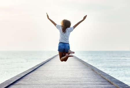 Rückansicht Mädchen auf dem Pier Springen. Freiheit Konzept