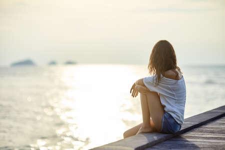 Młoda piękna kobieta siedzi na molo korzystających zachód słońca z miejsca na kopię