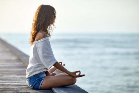 pier: Woman meditating in Lotus Pose on pier with the sea view. Padmasana. Relax concept Stock Photo