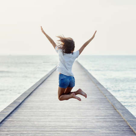Back view of jumping girl on the pier. Freedom concept Stock Photo