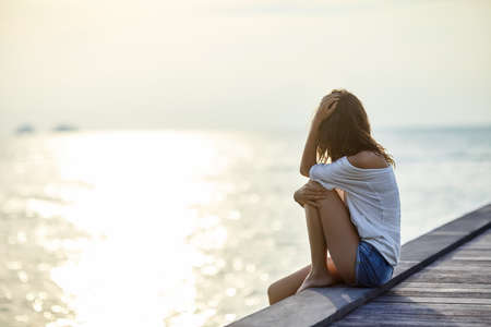 introvert: Young beautiful woman sitting on the pier enjoying sunset with copy space