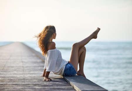 섹시 한 아름 다운 여자 바다보기와 부두에서 휴식. 휴가 개념