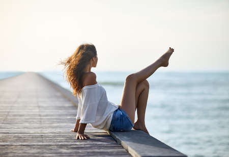 Sexy beautiful woman relaxing on pier with sea view. Vacation concept