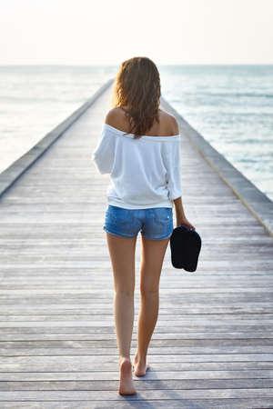 Achter mening van jonge mooie vrouw lopen op de pier. Volledige lengte portret