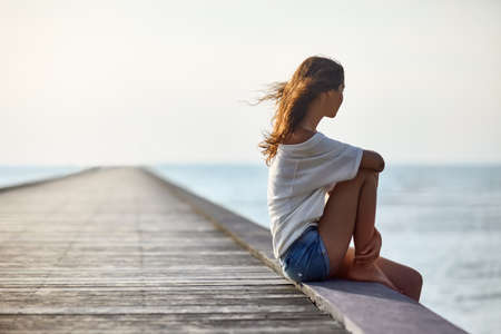Young beautiful woman sitting on the pier with copy space