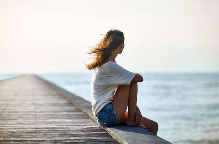 コピー スペースと桟橋に座って若い美しい女性