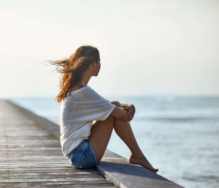 freedom of thought: Young beautiful woman sitting on the pier with copy space