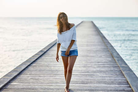 pier: Young beautiful woman walking on the pier