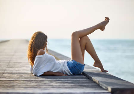 sea sexy: Sexy beautiful woman relaxing on pier with sea view. Vacation concept