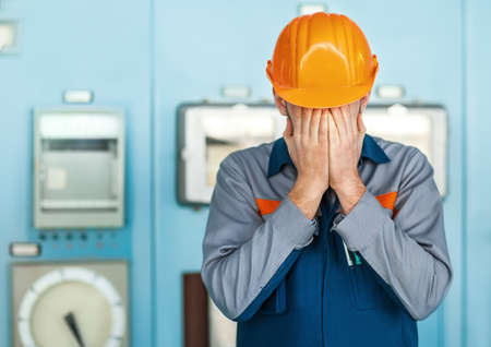 anonymous people: Portrait of stressed despair engineer closed face by two hands