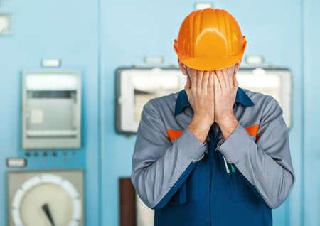 Portret van beklemtoonde wanhoop ingenieur gesloten gezicht door twee handen