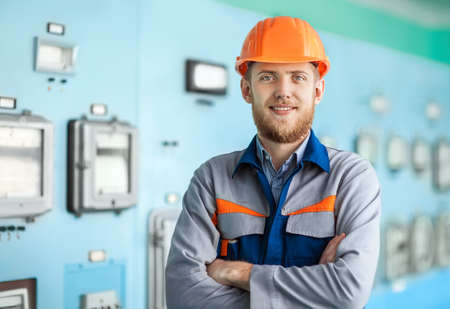 Portrait of young happy engineer at control room. Crossed arms Stock Photo