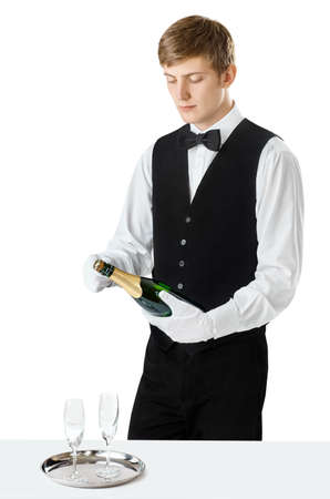 Portrait of young handsome waiter opening bottle of champagne isolated on white background