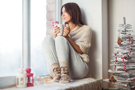 Happy beautiful woman drinking hot coffee sitting on window sill in christmas decorated home. Holiday concept Stock Photo
