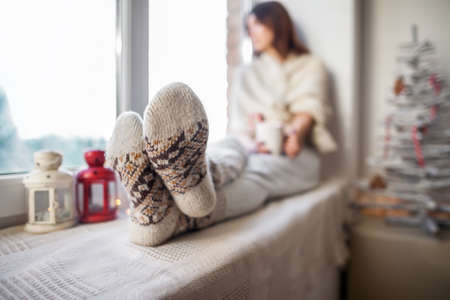 woman foot: Young beautiful woman relaxing on window sill in christmas decorated home. Focus on foot