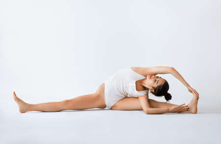 Young woman doing yoga asana revolved head to knee pose. Parivrtta Janu Sirsasana