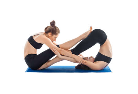 Partner Yoga isolated on white background. Two young women doing yoga asana.