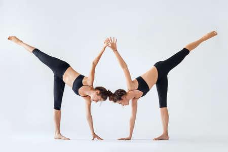 chandrasana: Two young women doing yoga asana Ardha Chandrasana. Half Moon Pose