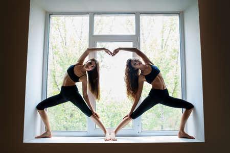 simbolo de la mujer: Dos mujeres hermosas jóvenes haciendo yoga asana mostrando el símbolo del corazón en el alféizar de la ventana