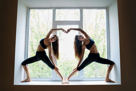 simbolo de la mujer: Two young beautiful women doing yoga asana showing heart symbol on window sill