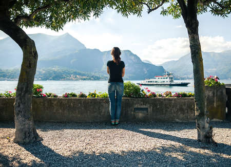 Back view of young woman relaxing on scenic quay of mountain Lake Como in Italy. Stock Photo