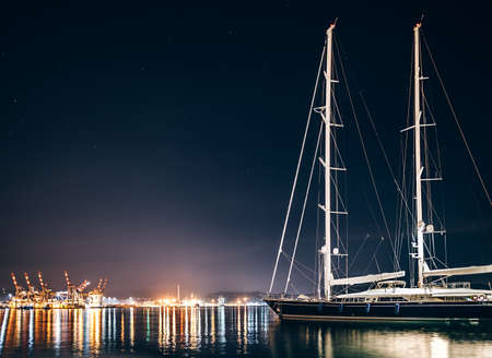 Luxury yacht in La Spezia harbor at night with reflection in water. Italy Stock Photo