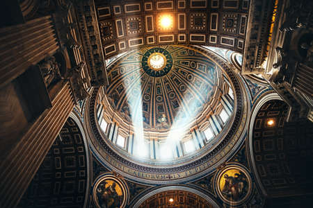architectural interiors: VATICAN, ROME, ITALY - JUNE 4, 2016: Interiors and architectural details of St. Peter Basilica with sun rays in Vatican, Italy
