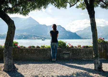 pier: Back view of young woman relaxing on scenic quay of mountain Lake Como in Italy. Stock Photo