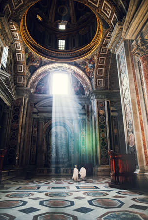 vatican city: VATICAN, ROME, ITALY - JUNE 4, 2016: cardinals back view in interiors of St. Peter Basilica with sun rays