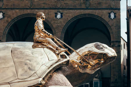 Florence, Italy - September 07, 2016: Golden turtle - sculpture Searching for Utopia by Belgian artist Jan Fabre on the Piazza della Signoria