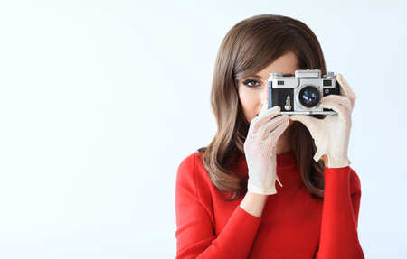 Retro style portrait of young beautiful woman taking photo with camera on white background with copy space Stock Photo