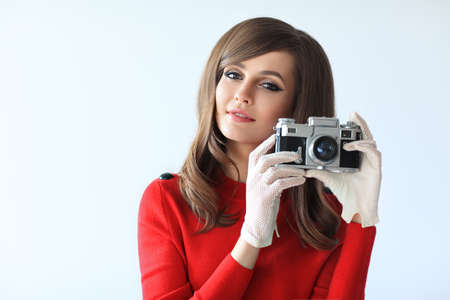 sixties: Portrait of young beautiful woman with photo camera in retro style on white background Stock Photo