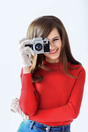 sixties: Retro style portrait of young beautiful woman taking photo with camera on white background Stock Photo