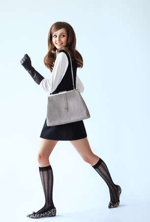 Full length fashion portrait of running beautiful woman witg bag in retro style