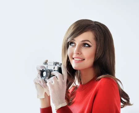 sixties: Portrait of young beautiful woman whith photo camera in retro style on white background Stock Photo
