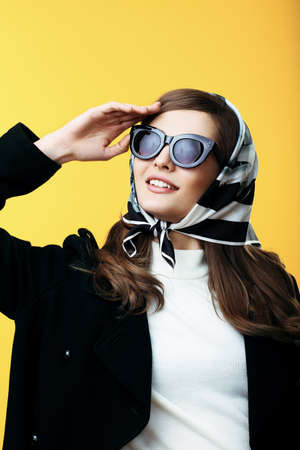 sixties: Fashion retro style portrait of young beautiful woman in sunglasses on yellow background