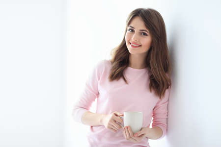 Smiling beautiful woman with cup of coffee on white background. Copy space Stock Photo