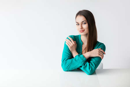 Beautiful young woman portrait sitting at the table on white background. copy space