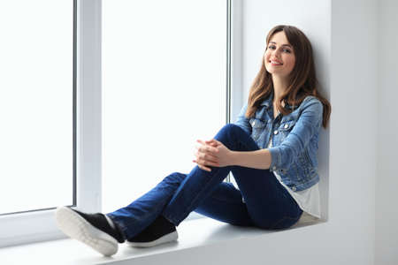 Smiling beautiful woman relaxing on window sill. Wellbeing concept