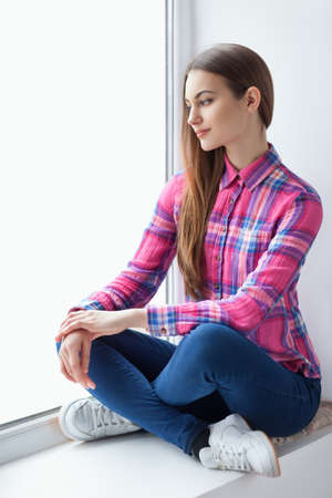Young smiling woman sitting on window sill. Relax concept photo