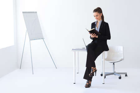 woman business suit: Portrait of young beautiful business woman reading notebook in the office