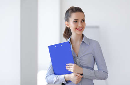 Happy beautiful business woman with clipboard in the office