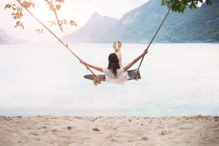 Carefree happy woman on swing on beautiful paradises beach in Thailand Фото со стока - 75254090