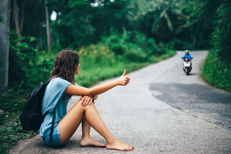 Young beautiful woman hitchhiking sitting on road barefoot. Travel concept Stock Photo