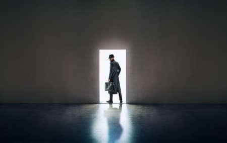 Man silhouet in hoed en regenjas staan in het licht van de deur van de deur in een donkere kamer Stockfoto