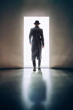 Man silhouette walking away in the light of opening door in dark room. escape concept