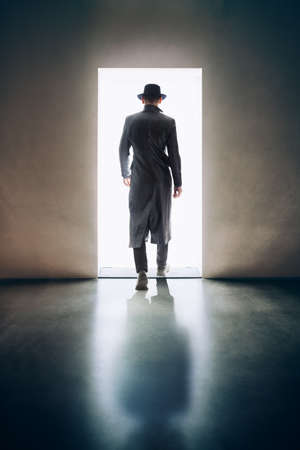 Man silhouette walking away in the light of opening door in dark room. escape concept Banco de Imagens - 76235979