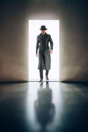Man silhouette coming from the light of opening door in dark room. mystery concept