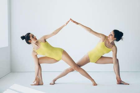 Two young beautiful women doing yoga asana extended side angle pose ( Utthita Parsvakonasana )