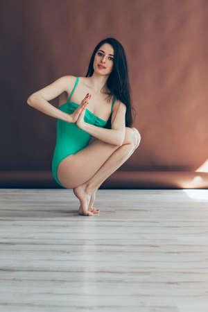 Young beautiful woman doing yoga asana tiptoe pose prapadasana variation on studio